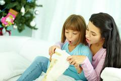 Mother and daughter looking into Christmas stocking Stock Photos