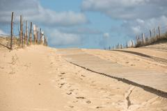 Wooden footpath through dunes at the ocean beach Stock Photos