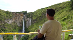 Young man backpacker sit and look at Sipiso-Piso waterfall Stock Footage