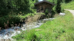 Weathered barn on a small stream in European alps. Schwarzachtal valley  Stock Footage