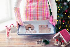Closeup of woman with gingerbread house on pan Stock Photos
