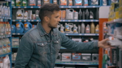 Car servicing, man choose paper air filter in supermarket. A lot of car good in Stock Footage