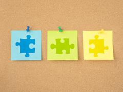 Puzzle pieces on message board Stock Photos