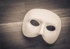 White theatre or carnival mask on wooden table Stock Photos