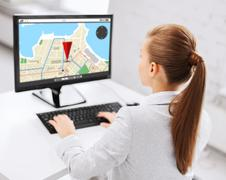 Businesswoman with gps navigator map on computer Stock Photos