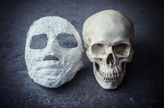 Human skull and white face mask on stone background. Stock Photos