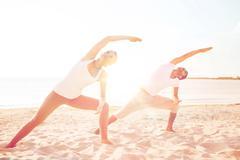 Couple making yoga exercises outdoors Kuvituskuvat