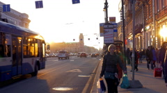 At sunset on sidewalk walking people, on a busy road drive cars and buses Stock Footage