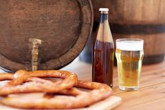 Close up of beer barrel, glass, pretzel and bottle Stock Photos