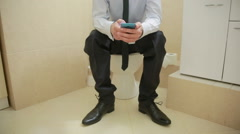 Male businessman watches the news on the phone sitting on the toilet Stock Footage