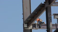 Close up of steel workers laying a beam while strapped in to the beam line vi Stock Footage