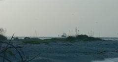 Slow-motion Fishing boat cruising behind Boca Grande Beach, Florida. Stock Footage