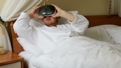 Man on the bed looks Virtual Reality Headset Stock Footage
