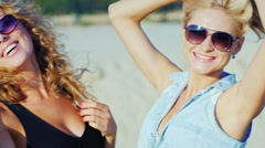 Two sexy woman posing for the camera at the beach, summer sunny day Stock Footage