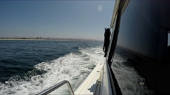 Looking stern of motor yacht under way on starboardwith Newport Beach coast  Stock Footage