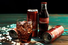 Can and a glass of iced Coca-Cola on a wooden table. Stock Photos