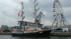 Sailing ship next to fun fair at Rostock Harbor during Hanse Sail weekend. Stock Footage