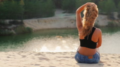 Young woman sitting on the beach, admiring the lake at sunset. View from the Stock Footage