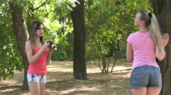 Girl photographer with a film camera taking pictures of her sister Stock Footage
