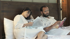 Young couple in bathrobes reading book and magazine lying on bed at home Stock Footage