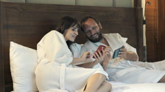 Young couple in bathrobes using smartphones while lying on bed at home  Stock Footage