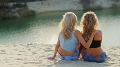 Romantic couple of two women sitting in an embrace on the beach, gently hugging Stock Footage