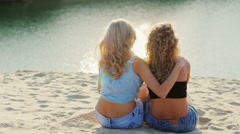 Couple young women holding each other sitting on the bank. Admire the beautiful Stock Footage