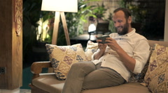Young man playing game on smartphone sitting on sofa at night Stock Footage