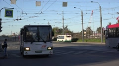 Back-to-back coupled 2-car tram heads to terminus and diesel bus leaves that Stock Footage