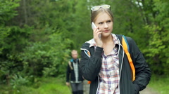 Boy walking with sticks in the forest while his girlfriend talking on cellphone Stock Footage