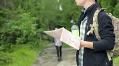 Girl walking with sticks in the forest while boy reading map, steadycam shot Stock Footage