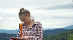 Girl reading map and drinking energy drink while standing with a boy on the hill Stock Footage
