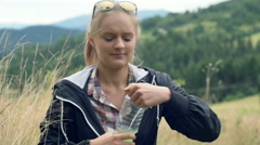 Pretty girl standing on the hill in the meadow and drinking energy drink Stock Footage