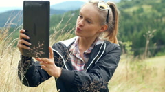 Pretty girl standing in the meadow and doing selfies on tablet Stock Footage