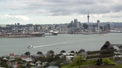 Auckland from Devenport with young couple on seat Stock Footage