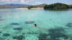 Woman swimming in crystal clear water in paradise ocean in Indonesia Stock Footage