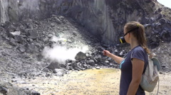 Young woman looking at smoking fumaroles on active Sibayak volcano and thumbs up Stock Footage
