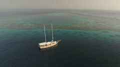 Aerial view of anchored sailing boat between coral reefs - Red Sea Stock Footage