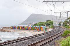 Multi-colored beach huts at St. James with railroad passing by Stock Photos