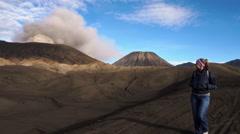 Backpacker female traveler walking near active smoking Bromo volcano Stock Footage