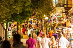 AGIOS NIKOLAOS, GREECE - JULY 28, 2012: Tourists walking along shopping stree Stock Photos
