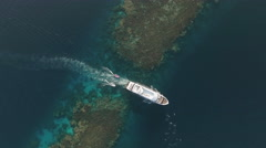 Aerial view of boat and dolphins, passes through to coral reef lagoon Stock Footage