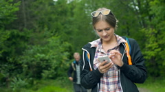 Boy walking with sticks and his girlfriend browsing internet on smartphone Stock Footage