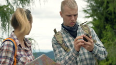 Couple using map and compass while checking the direction in the forest Stock Footage