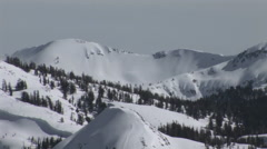 Pan-down shot of hikers moving up a steep and snowy mountain slope. Stock Footage