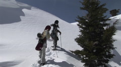 Zoom-in shot of two people on snowshoes heading up a steep and snowy slope with Stock Footage