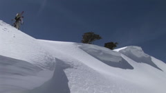 Long-shot of hikers ascending a snowy mountain with snowboards on their backs. Stock Footage
