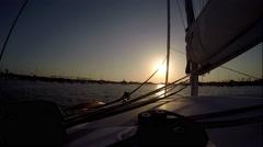 Sunset  with sun on jib sheet sailing catamaran motoring into harbor. Stock Footage