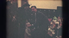 1959: a man squatting in front of a little boy and adjusting his suit and coat Stock Footage
