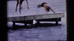 1961: two young men in shorts diving off a dock into the water below CAMDEN, NEW Stock Footage